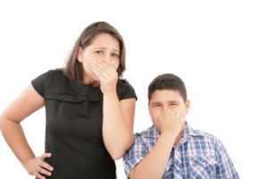 mother and son holding their noses